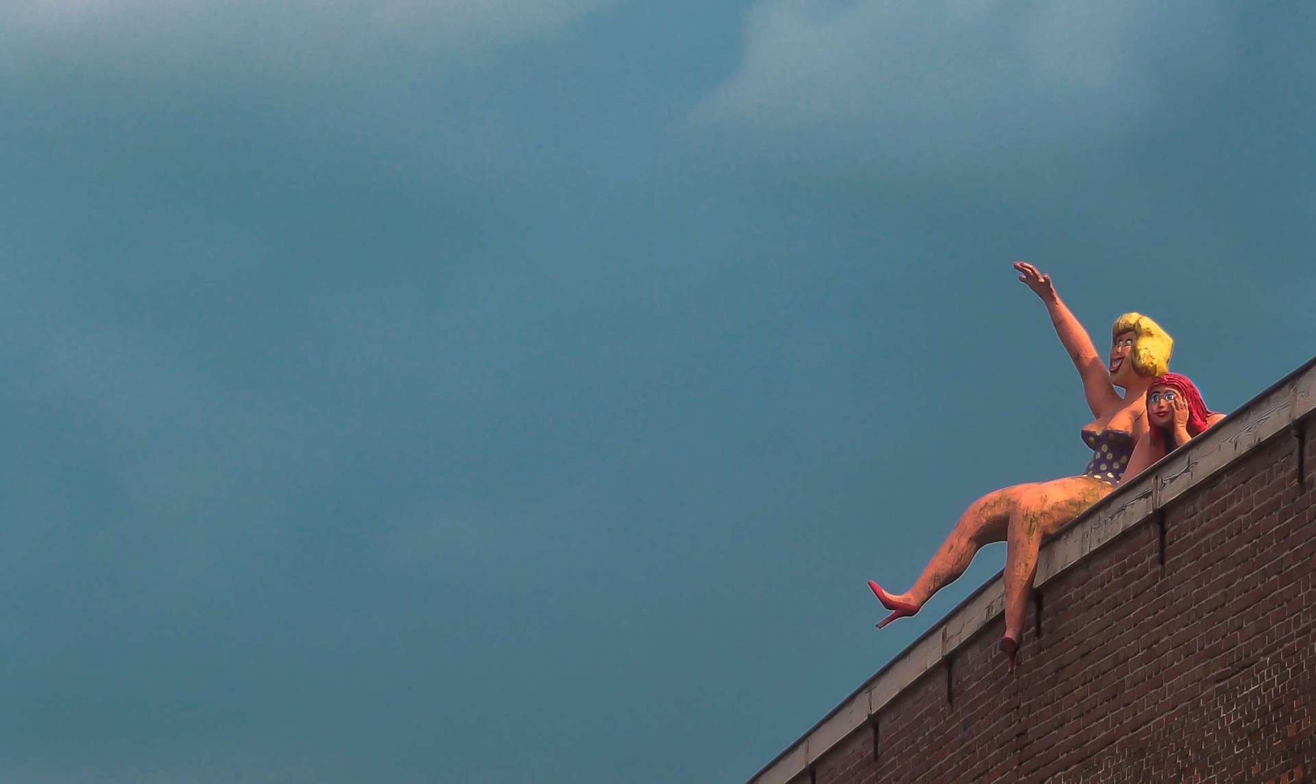 Two sex dolls sitting on a rooftop.